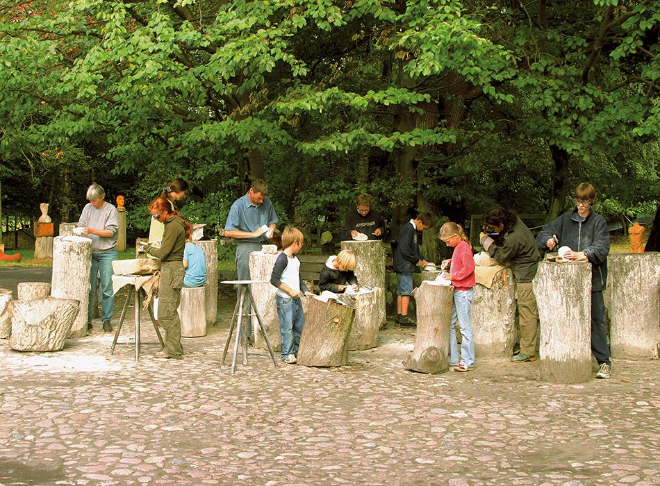 Kinder und Erwachsene vor Bäumen beim Steinhauern