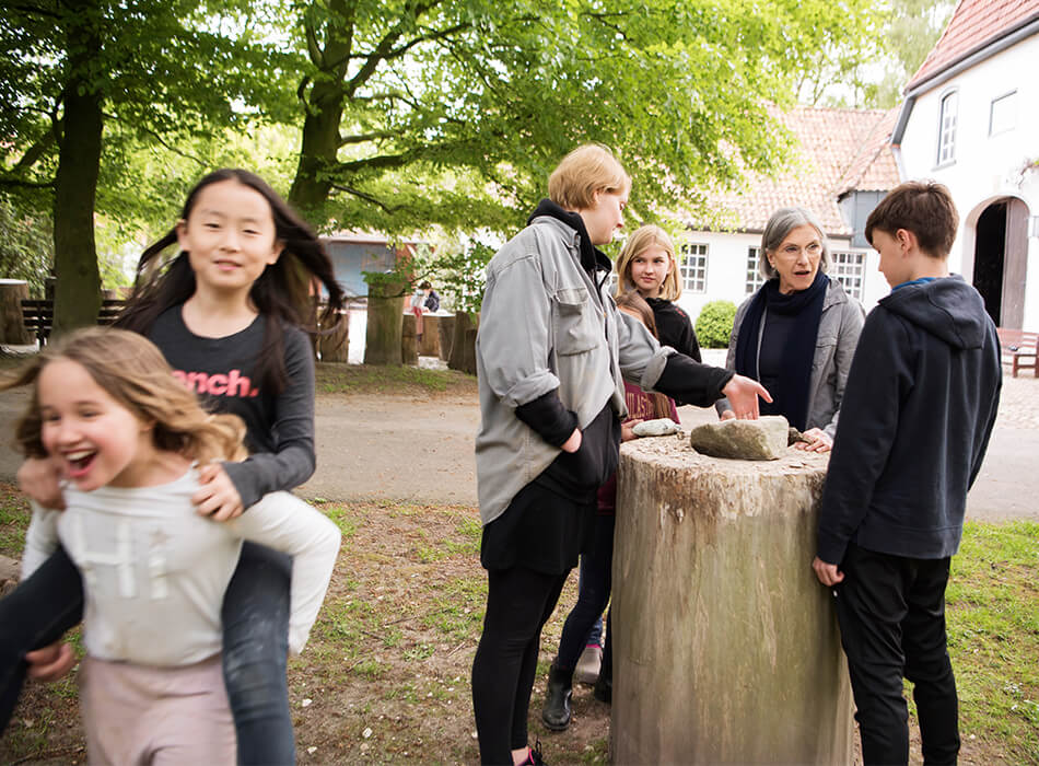 Kinder spielen und beraten am Steinhauern-Kunstwerk